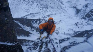 Guy reaching the belay below the third pitch