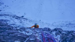 Guy pulling over the roof on the crux pitch